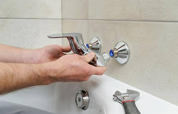 Hands installing faucet over bath tub